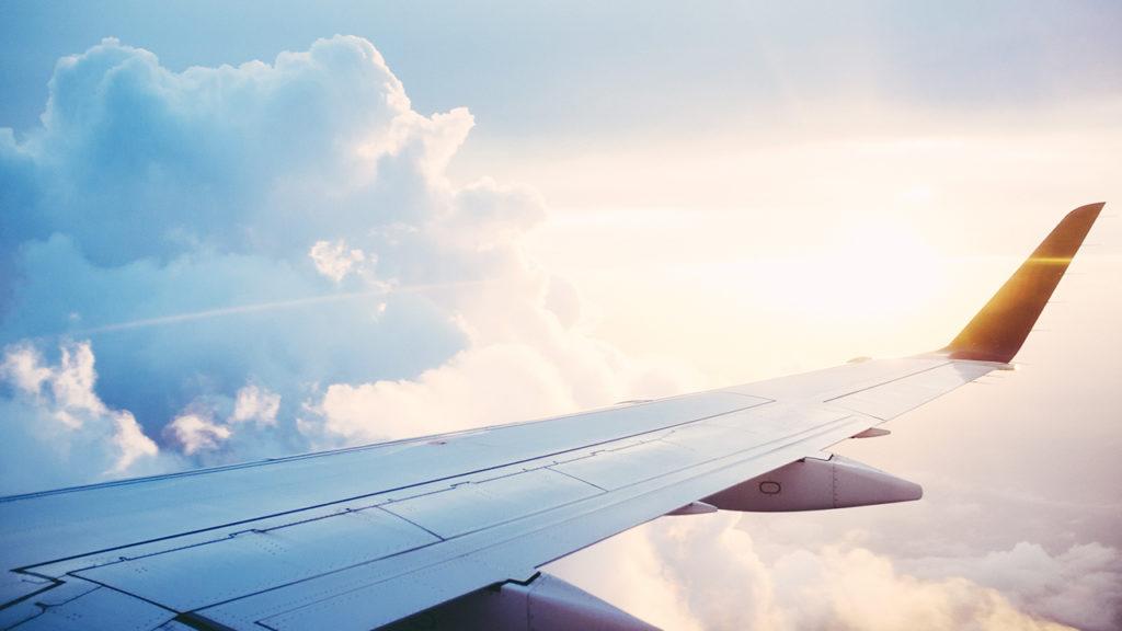 飛んでいる飛行機の翼の画像
